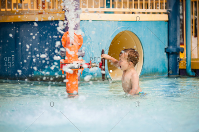 Little boy playing in the pool with a hydrant