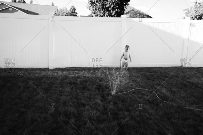 Little boy watching the water sprinkler in the garden