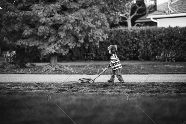 Boy mowing the grass with a toy lawn mower
