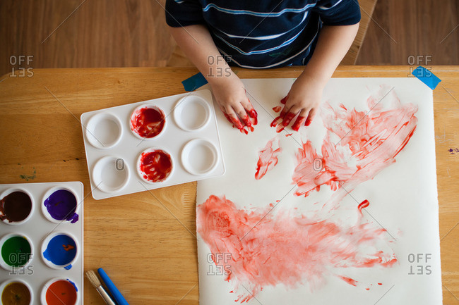 Boy painting with his messy fingers on a paper