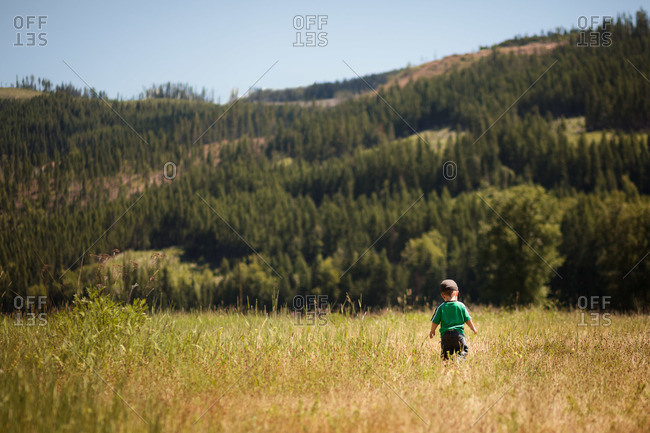 Young boy walking in a grassy field