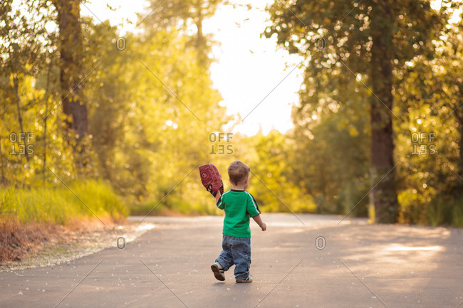 Young boy walking on a road with a baseball glove