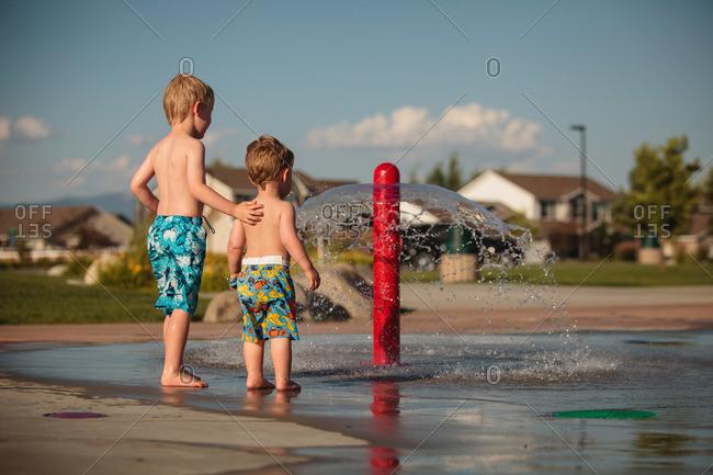 Boys standing at a splash pad on a street