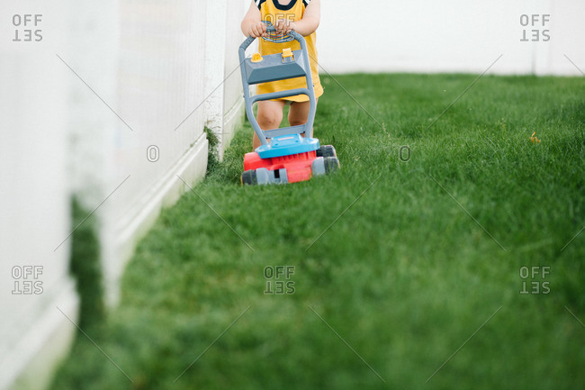 Young child pulling a toy lawn mower