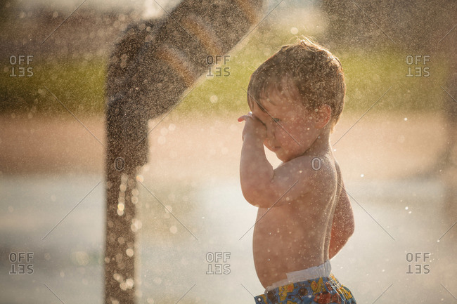 Young boy rubbing his eyes at a splash pad