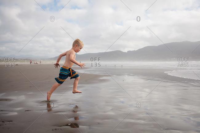 Young boy running on a muddy beach