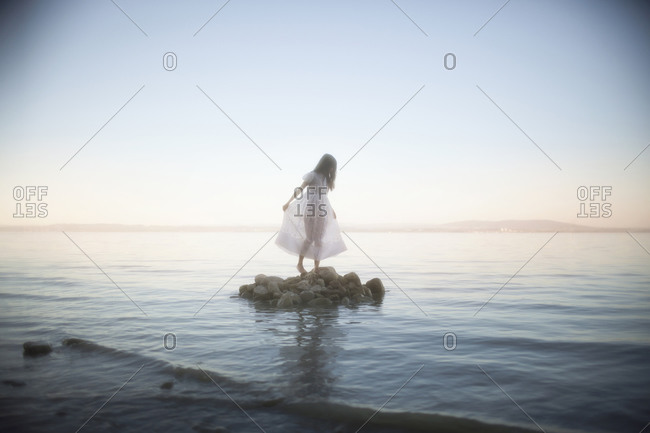 A girl walking on a rock island in the middle of a lake at sunset