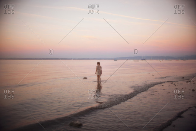 A girl walking into a lake during sunset