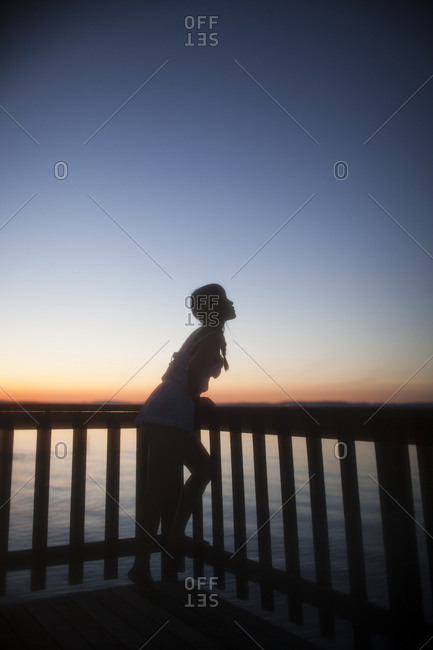 A girl is standing on a balcony overlooking the sea
