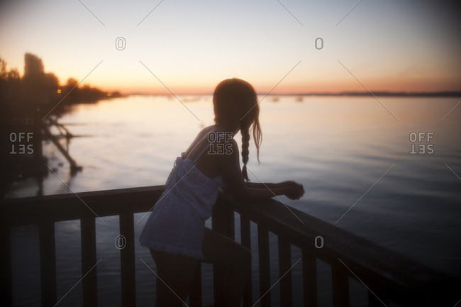 A girl watching the sunset from her balcony overlooking the sea