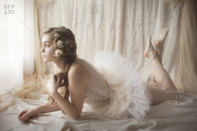 A ballerina dressed in white looking out of the window