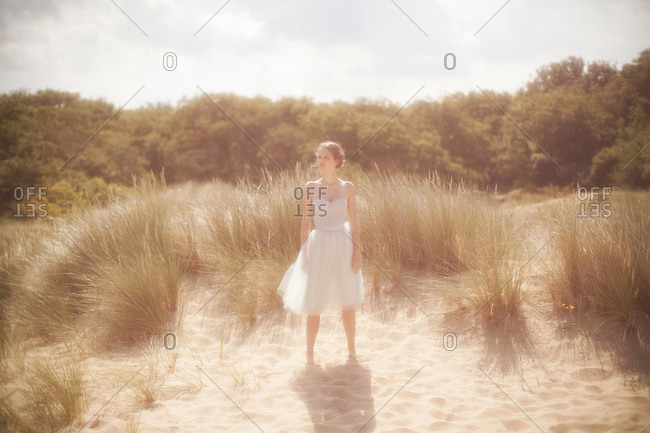 A young girl standing on a sand dune