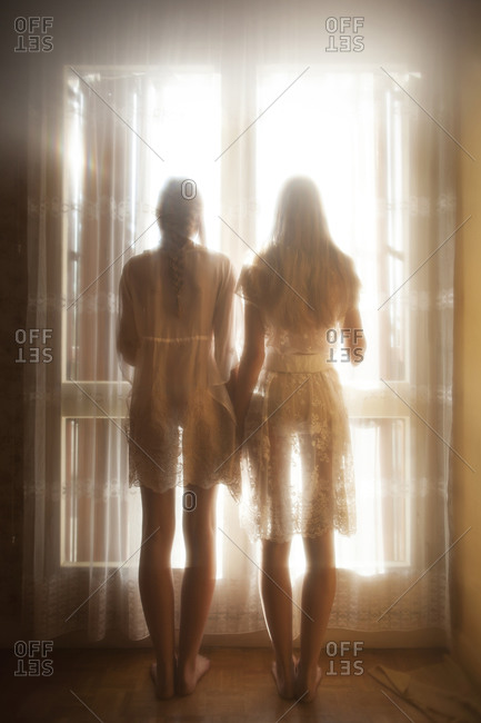 Two girls holding hands standing in front of a window
