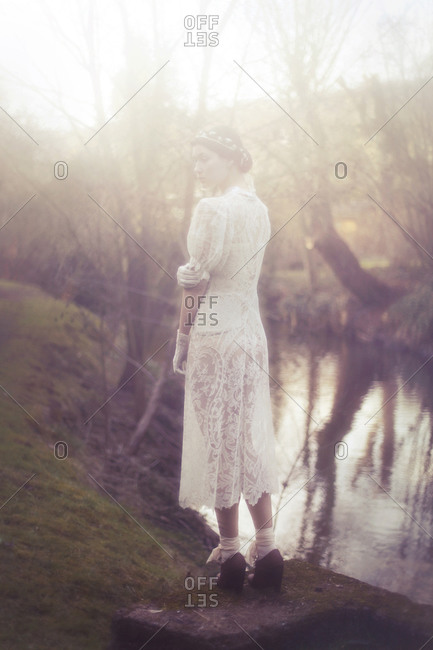 A girl standing in a lace white dress by the river