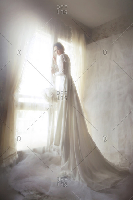A girl in a long wedding dress by the window