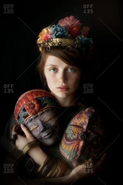 A girl dressed in black holding two masks with flowers in her hair