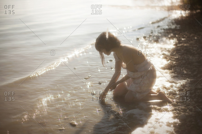 A girl kneeling by the lake side