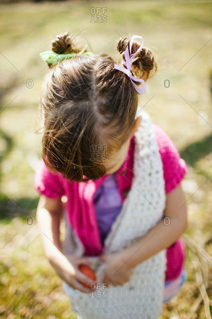 Girl putting Easter eggs in her bag at an egg hunt