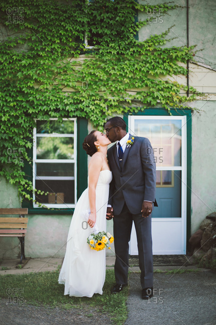 Newlywed couple posing in front of an ivy covered building