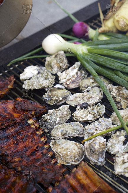 Ribs, oysters and vegetables on a grill