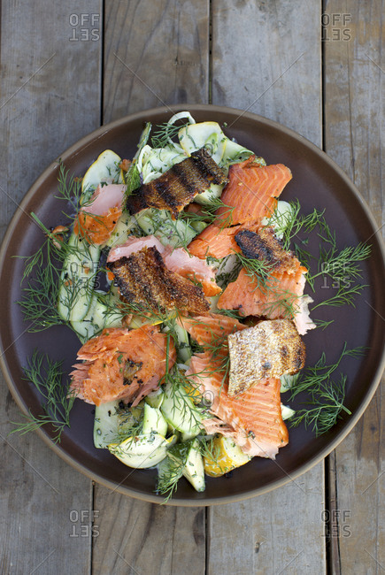 Grilled salmon over vegetables served outdoors on a rustic wood table