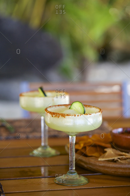 Margaritas on a wood table in a tropical setting