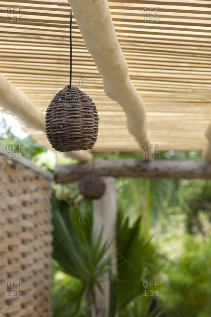 Hanging woven light in an outdoor tropical setting