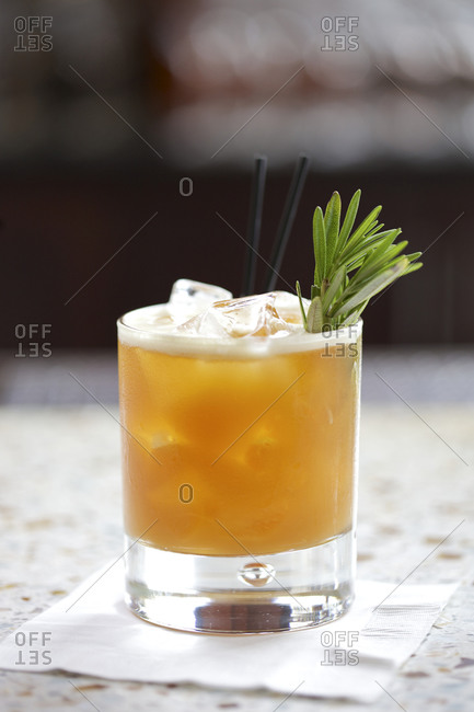 Cocktail garnished with a rosemary sprig