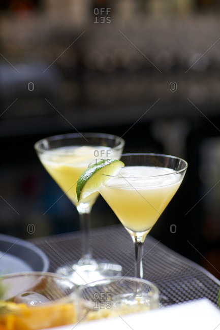 Two cocktails in the prep area of a bar