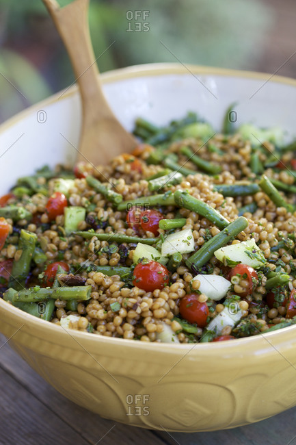 Vegetable and barley salad outdoors on rustic wood table