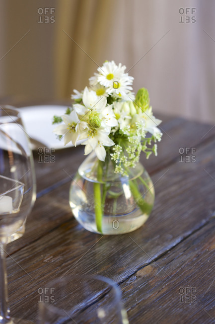 Small vase of flowers set on rustic wood table
