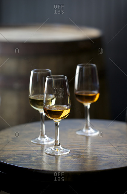 Glasses of whiskey in front of barrel
