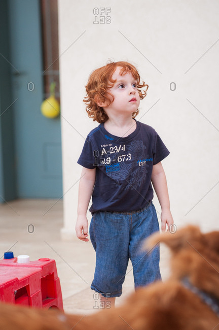 Redhead boy standing on a terrace