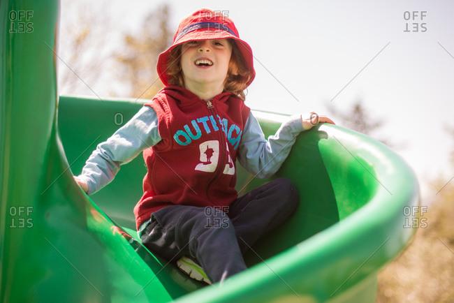 Redhead boy sliding down a spiral slide on playground