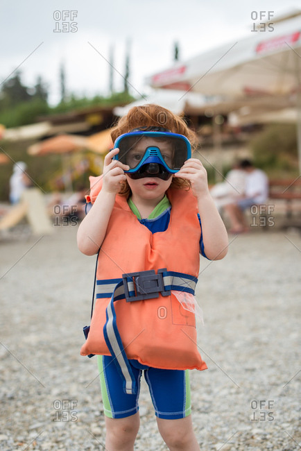 Redhead boy standing on a beach and wearing diving mask