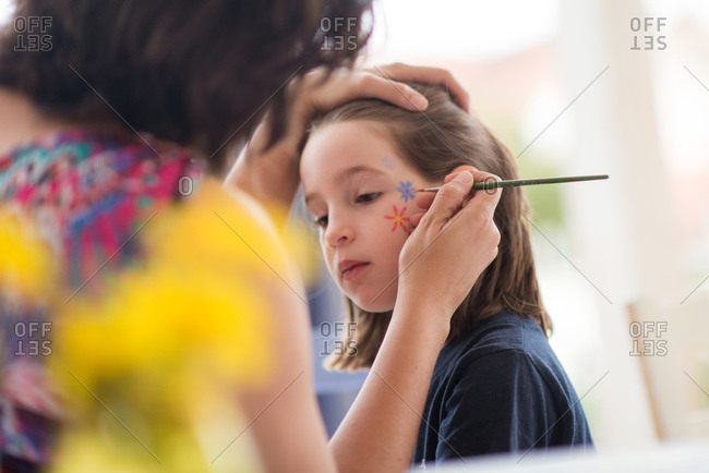 Woman preparing face painting for a girl