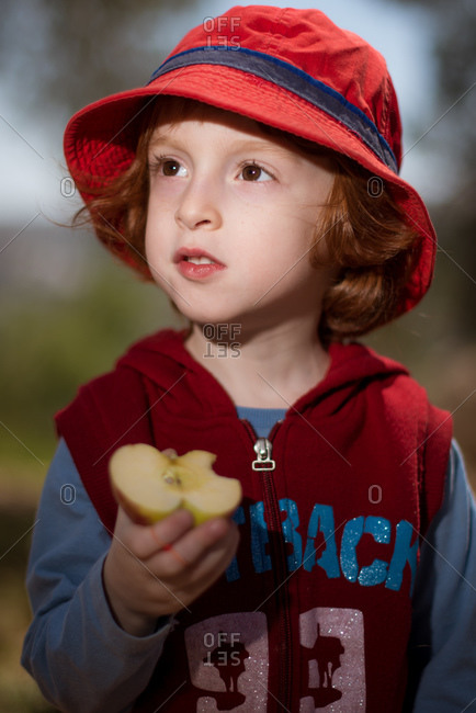 Redhead boy eating a halved apple