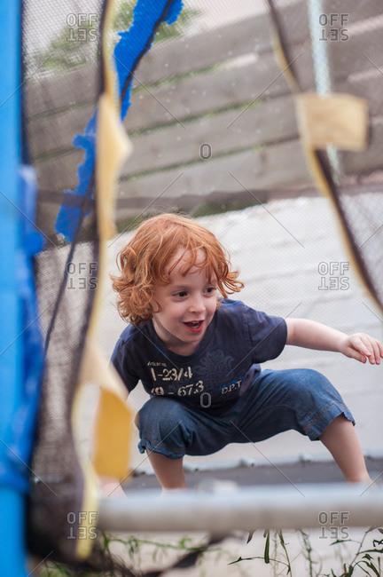 Redhead boy playing on trampoline
