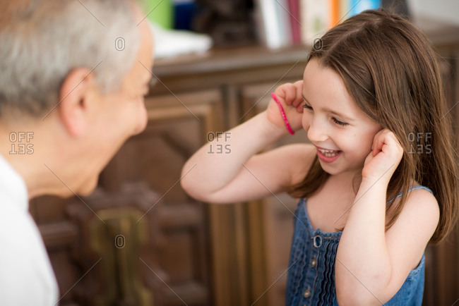 A grandfather and his granddaughter having fun in living room