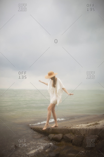 A girl walking by the lake on a stormy day
