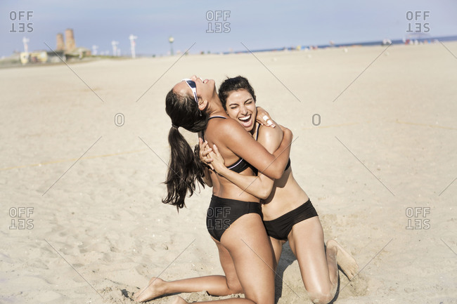 Two young women cheering at beach volleyball court