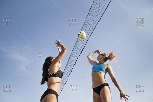 Low angle view of girls hitting the volleyball over the net
