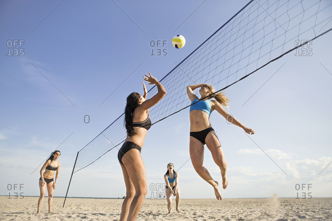 Beach volleyball players hitting the ball over the net
