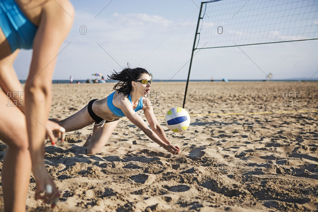 Beach volleyball player dives for a shot