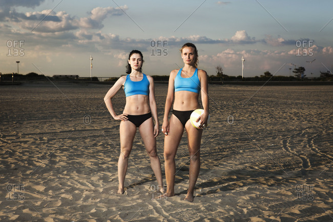 Volleyball players standing on a sandy beach