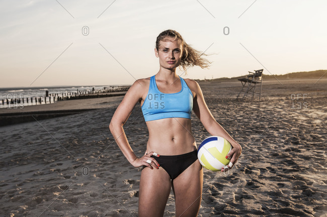 Volleyball player holding a ball on a sandy beach