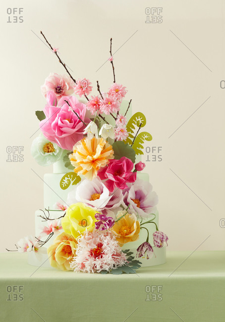 Three-tiered cake decorated with paper flowers