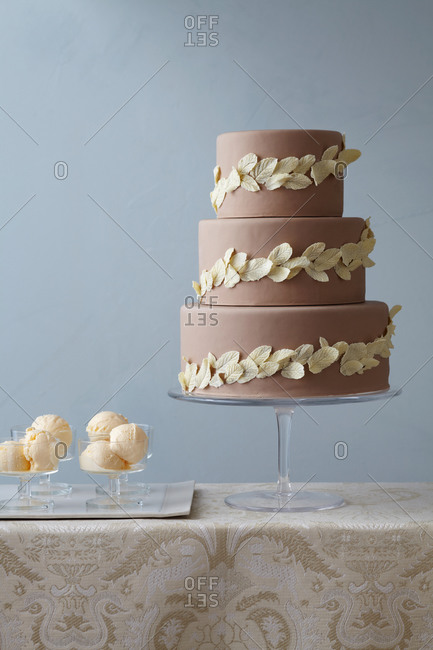 Three tiered cake decorated with white chocolate leaves