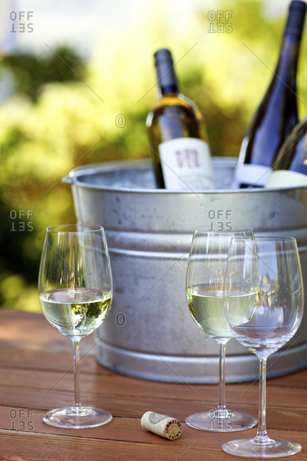 White wine in glasses with bottles in an ice bucket