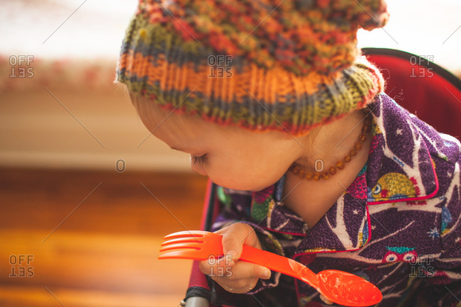 Young girl holding plastic spoon and looking down